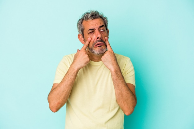 泣いて、何かに不満、苦痛と混乱の概念の青い背景に孤立した中年の白人男性。