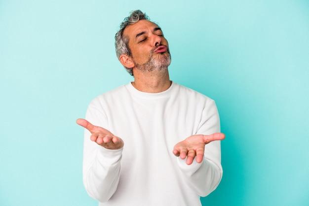 青い背景に孤立した中年の白人男性は、唇を折り、手のひらを持って空気のキスを送信します。