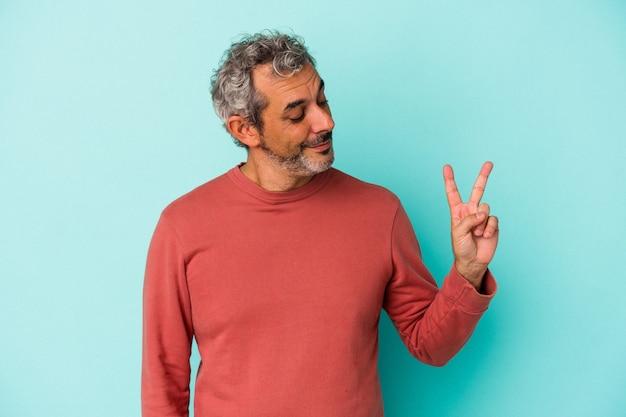 指で平和のシンボルを示す、楽しくてのんきな青い背景に分離された中年の白人男性。