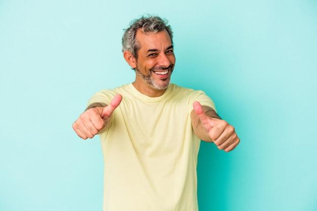 青い背景に孤立した中年の白人男性は、両方の親指を上げて、笑顔で自信を持っています。 Premium写真
