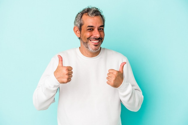 青い背景に孤立した中年の白人男性は、両方の親指を上げて、笑顔で自信を持っています。