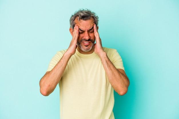 寺院に触れて頭痛を持っている青い背景に分離された中年の白人男性。