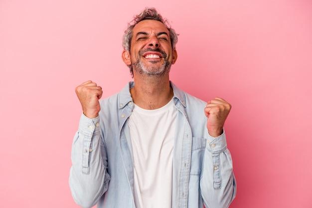 勝利、情熱と熱意、幸せな表現を祝うピンクの背景に分離された中年の白人男性。