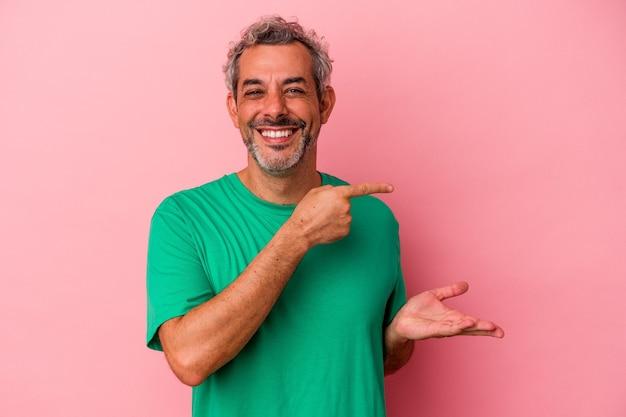 ピンクの背景に分離された中年の白人男性は、手のひらにコピースペースを保持して興奮しました。