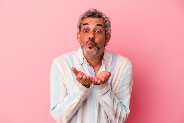 ピンクの背景に分離された中年の白人男性は、唇を折り、手のひらを持って空気のキスを送信します。