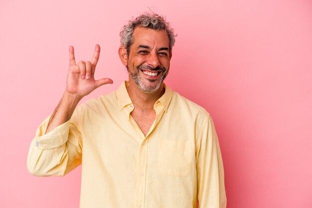革命の概念として角のジェスチャーを示すピンクの背景に分離された中年の白人男性。
