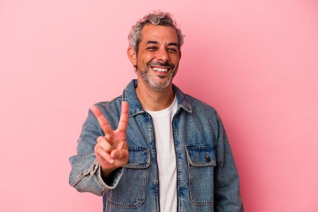 勝利のサインを示し、広く笑顔のピンクの背景に分離された中年の白人男性。