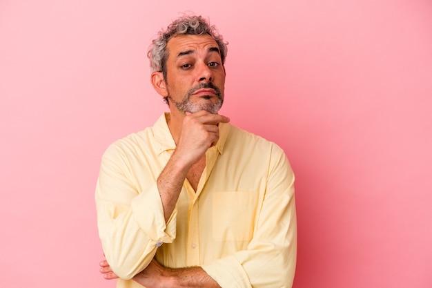 ピンクの背景に孤立した中年の白人男性は、疑わしい、不確かな、あなたを調べています。