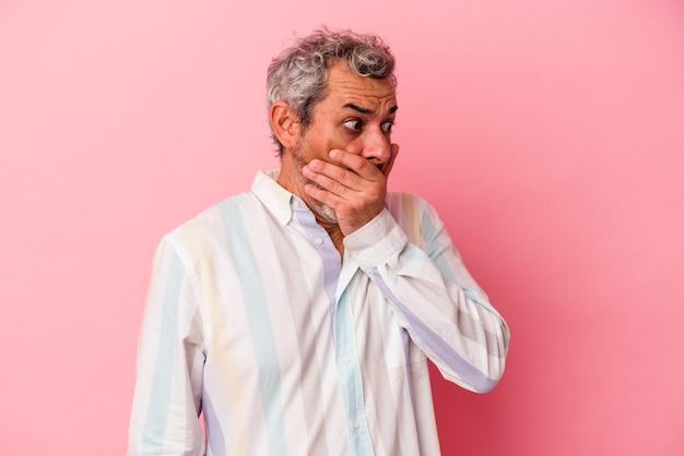 ピンクの背景に孤立した中年の白人男性は、手で口を覆うコピースペースを思慮深く見ています。