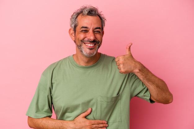 ピンクの背景に分離された中年白人男性はおなかに触れ、優しく微笑んで、食事と満足の概念。