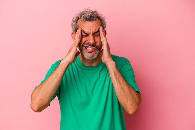 寺院に触れて頭痛を持っているピンクの背景に分離された中年の白人男性。