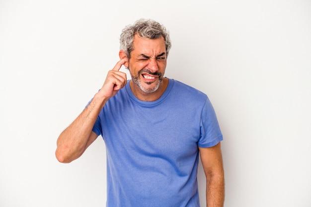 指で耳を覆っている白い背景に孤立した中年の白人男性は、大声で周囲にストレスと絶望的です。