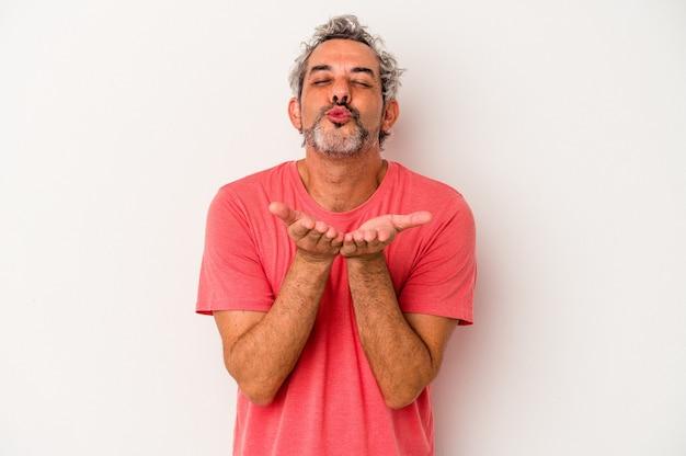 唇を折り畳み、空気のキスを送信するために手のひらを保持している白い背景で隔離された中年の白人男性。
