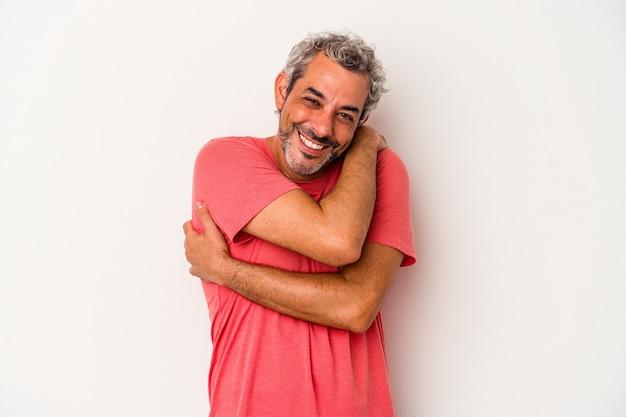 白い背景で隔離された中年の白人男性は、のんびりと幸せに笑って抱擁します。