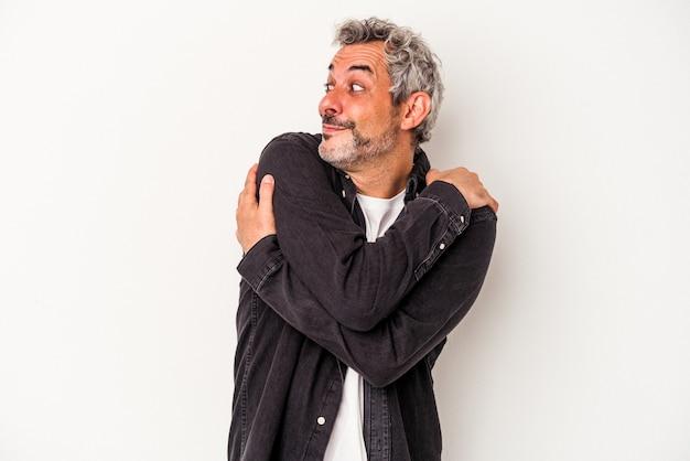 白い背景の抱擁に分離された中年の白人男性は、のんびりと幸せに笑っています。