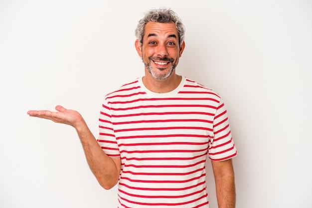 手のひらにコピースペースを示し、腰に別の手を保持している白い背景で隔離の中年白人男性。