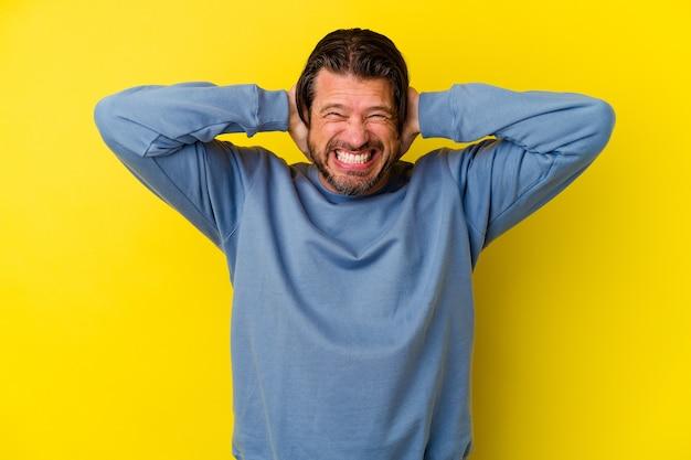 黄色の背景に孤立した中年の白人男性が、耳を手で覆い、大きすぎる音が聞こえないようにしています。