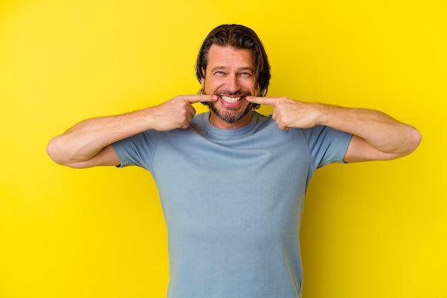 입에서 손가락을 가리키는 노란색 배경 미소에 고립 된 중 년 백인 남자.