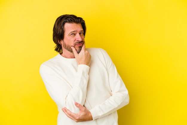 Кавказский мужчина среднего возраста, изолированные на желтом фоне, подозрительный, неуверенный, изучая вас.
