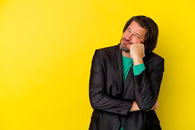Кавказский мужчина среднего возраста, изолированные на желтом фоне, который чувствует себя грустным и задумчивым, глядя на пространство для копирования.