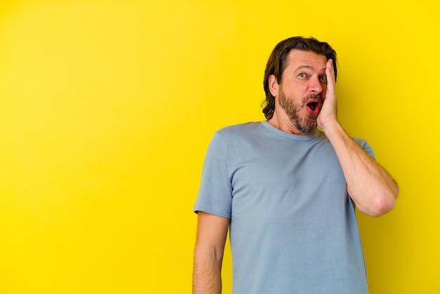 Кавказский мужчина средних лет, изолированные на желтой стене, потрясен из-за чего-то, что она видела.