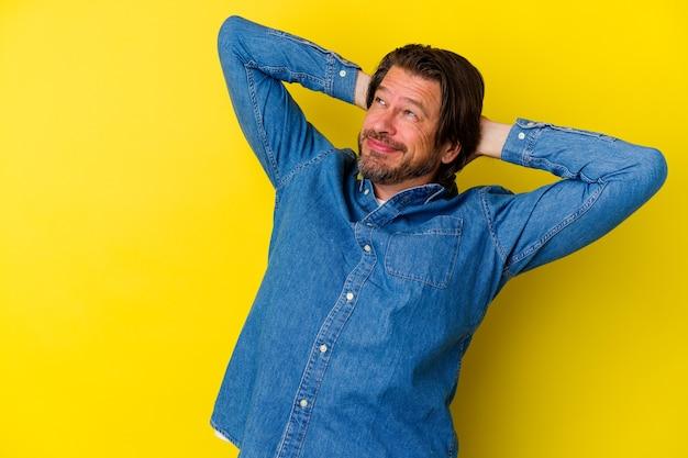 頭の後ろに手を置いて、自信を持って黄色の壁に孤立した中年の白人男性。