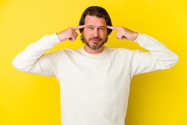 노란색 벽에 고립 된 중년 백인 남자는 작업에 초점을 맞추고 집게 손가락이 머리를 가리키는 유지.