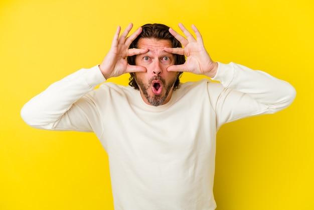 Кавказский мужчина среднего возраста изолирован на желтой стене, держа глаза открытыми, чтобы найти возможность успеха.