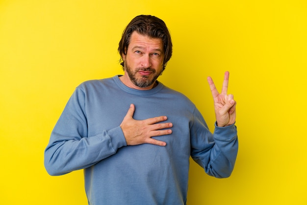 誓いを立て、胸に手を置いて、黄色の壁に孤立した中年の白人男性。