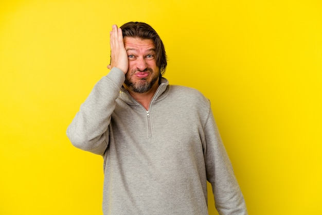 黄色い壁に孤立した中年の白人男性は、頭に手を置いて疲れていて非常に眠いです。