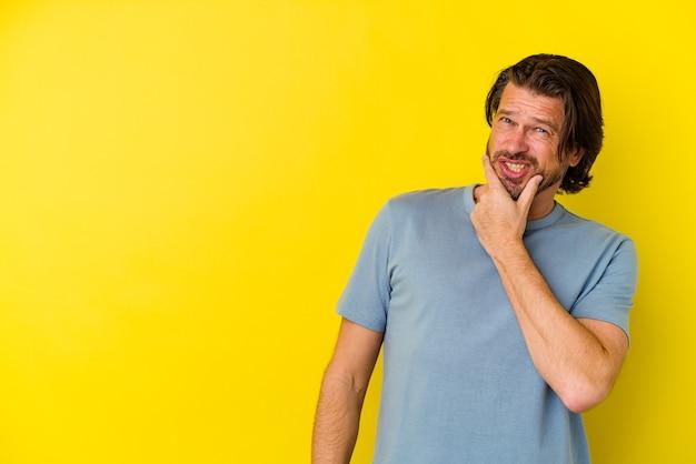 노란색 벽에 머리를 만지고, 생각 하 고 선택에 고립 된 중간 나이 백인 남자.