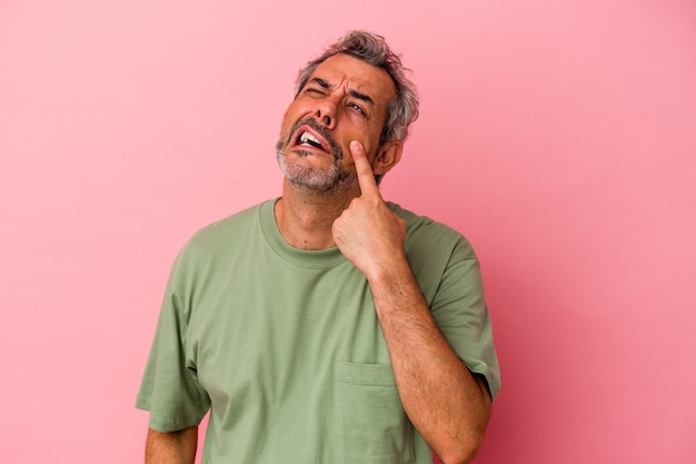 Middle age caucasian man isolated on pink background  crying, unhappy with something, agony and confusion concept.