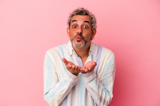 Middle age caucasian man isolated on pink background  folding lips and holding palms to send air kiss.