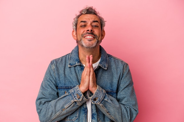 Middle age caucasian man isolated on pink background  holding hands in pray near mouth, feels confident.