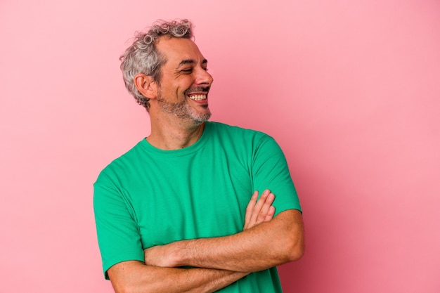 Middle age caucasian man isolated on pink background  smiling confident with crossed arms.
