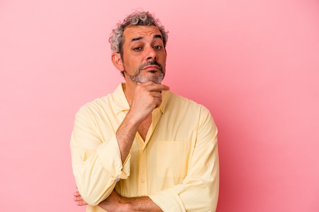 Middle age caucasian man isolated on pink background  suspicious, uncertain, examining you.