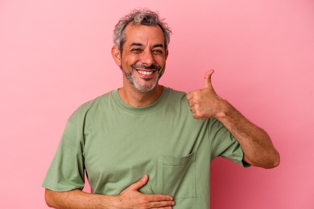 Middle age caucasian man isolated on pink background  touches tummy, smiles gently, eating and satisfaction concept.