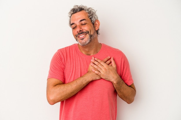 Middle age caucasian man isolated on white background  has friendly expression, pressing palm to chest. love concept.