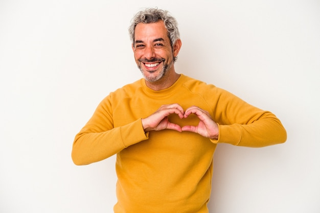 Middle age caucasian man isolated on white background  smiling and showing a heart shape with hands.