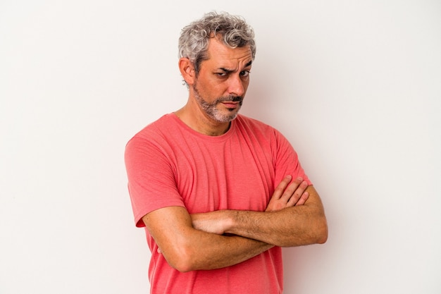 Middle age caucasian man isolated on white background  suspicious, uncertain, examining you.