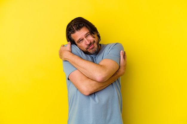 Middle age caucasian man isolated on yellow background hugs, smiling carefree and happy.