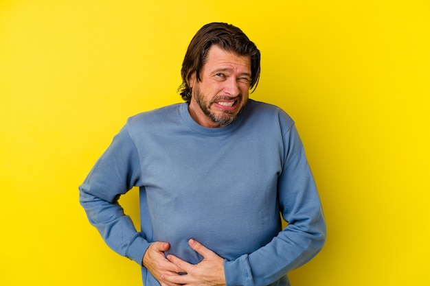 Middle age caucasian man isolated on yellow wall having a liver pain, stomach ache.