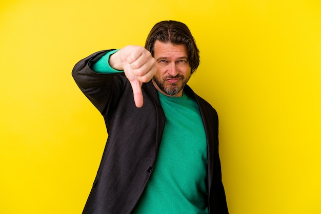 Middle age caucasian man isolated on yellow wall showing thumb down, disappointment concept.