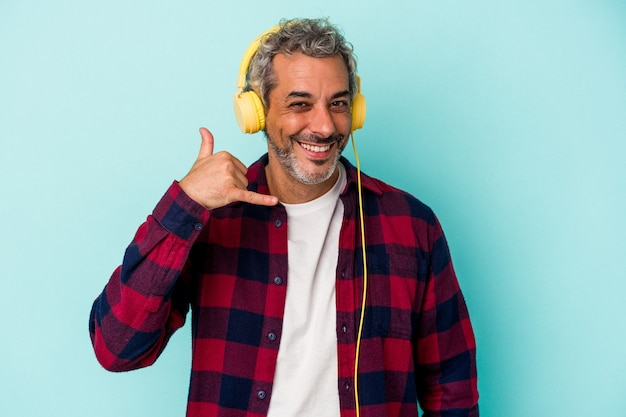 Middle age caucasian man listening to music isolated on blue background  showing a mobile phone call gesture with fingers.