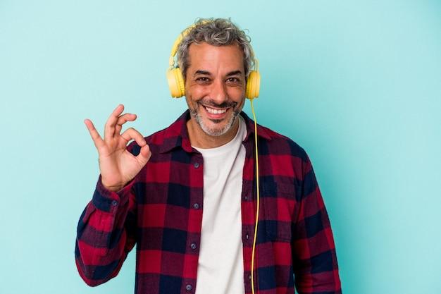 青の背景に分離された音楽を聴いている中年の白人男性は、陽気で自信を持って大丈夫なジェスチャーを示しています。