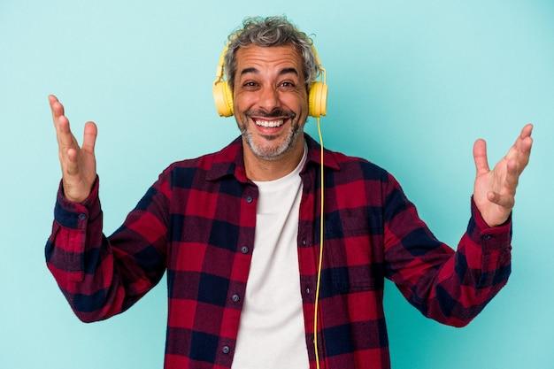 青い背景に分離された音楽を聴いている中年の白人男性は、嬉しい驚きを受け取り、興奮し、手を上げます。