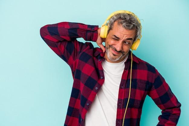 頭の後ろに触れて、考えて、選択をする青い背景に分離された音楽を聞いている中年の白人男性。