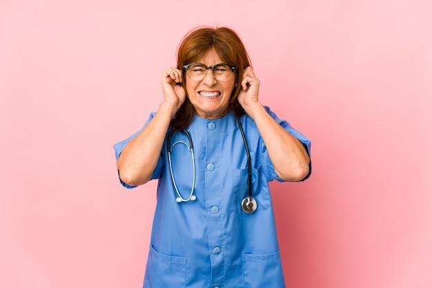 Женщина медсестры среднего возраста кавказская изолировала уши заволакивания руками.