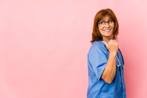 Женщина медсестры среднего возраста кавказская изолировала точки с пальцем большого пальца прочь, смеясь над и беззаботно.