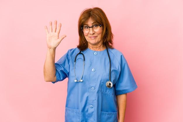 指で5番を見せて元気に笑っている中年白人看護婦。